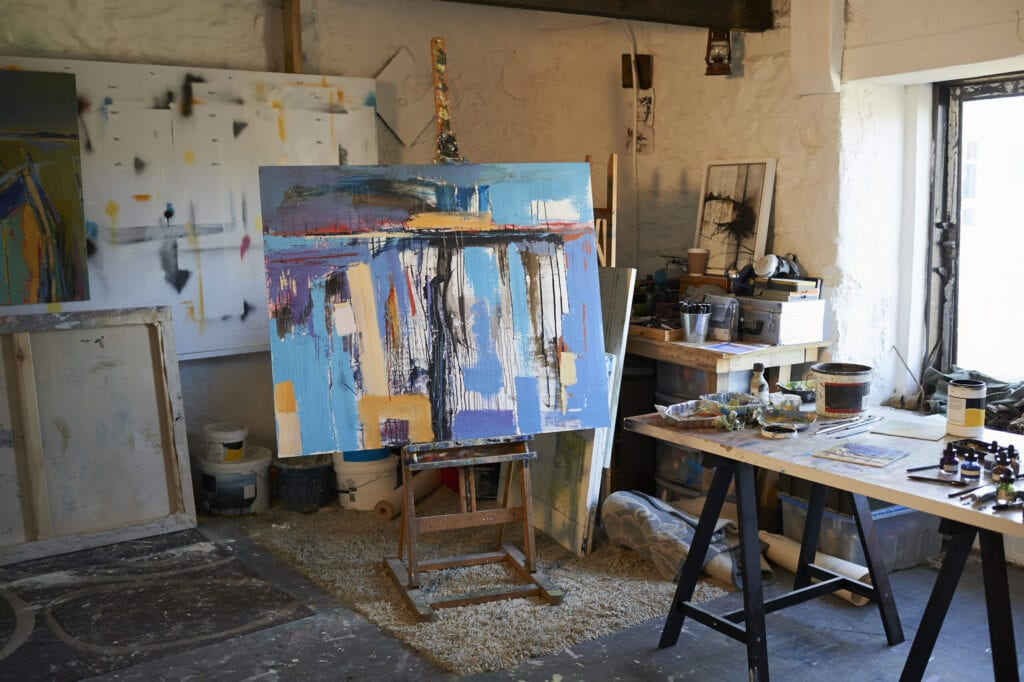 A large canvas painting on an easel in a creative artist studio.