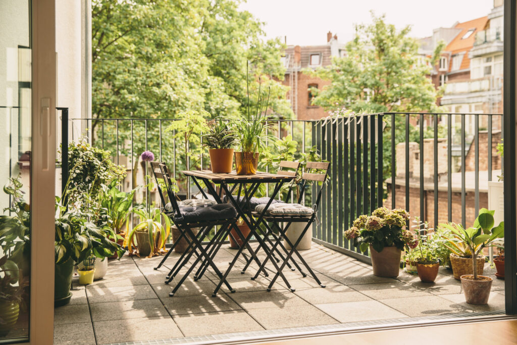 Balcony loggia in summer's bloom with bistro chairs and a view in the yard, Cologne, NRW, Germany