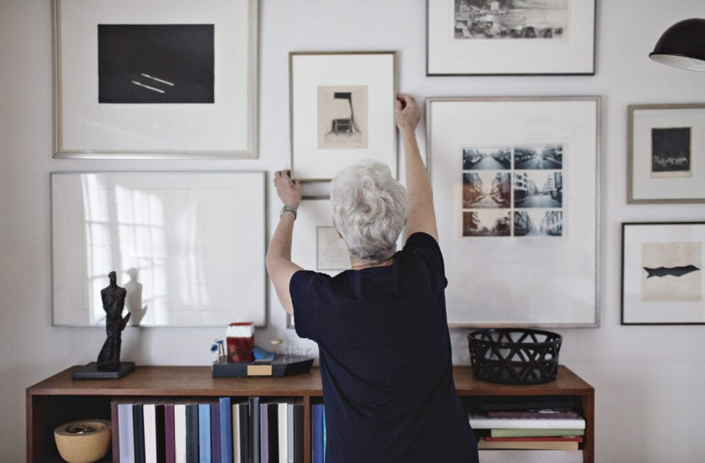 Woman hanging pictures on the wall, grey, beige, black, and white interior design