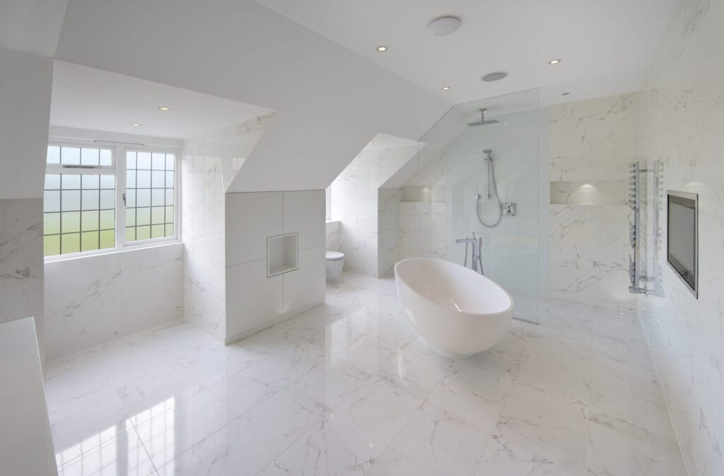large luxury white marble lined bathroom in an expensive home with a large oval bath. In the background is the show area behind a glass screen. A hint of green, adding a bit of colour to the scene, is visible through the frosted glass windows overlooking a garden. A large TV screen has been installed flush in the wall to the right. The square feature to the left of the bath are cupboards with a recess for decorative items in the centre. more lit recesses can be seen in the shower area.