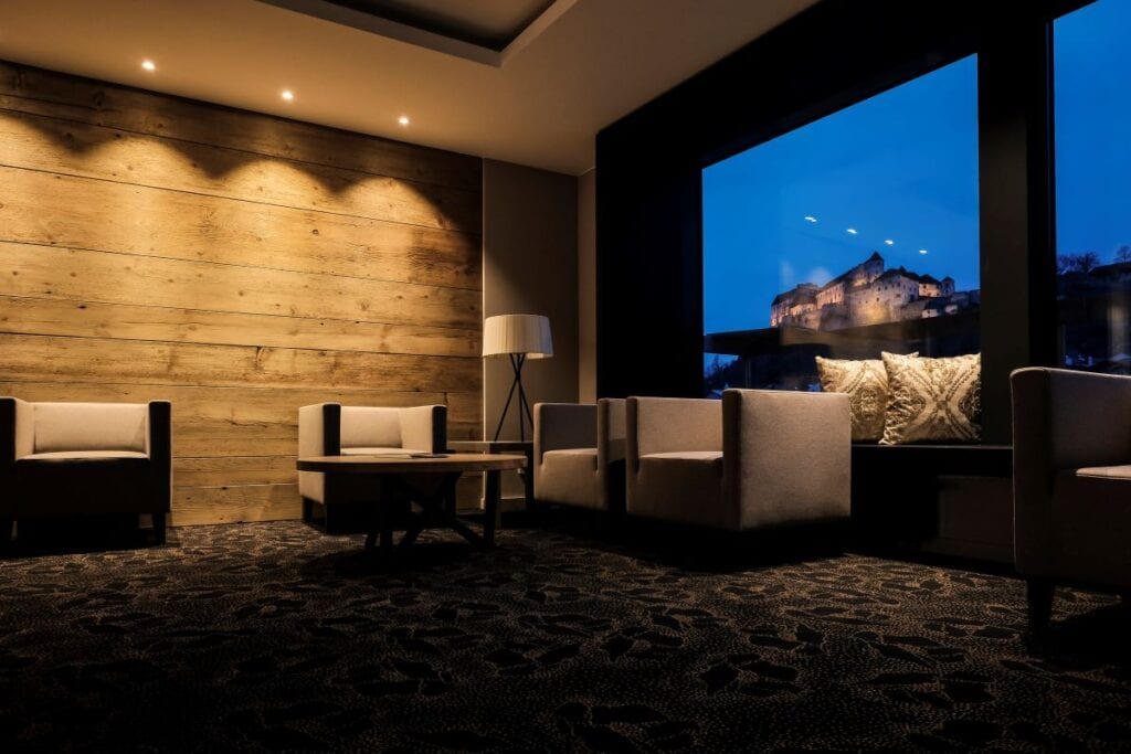 Living room has wood wall and view of castle at night