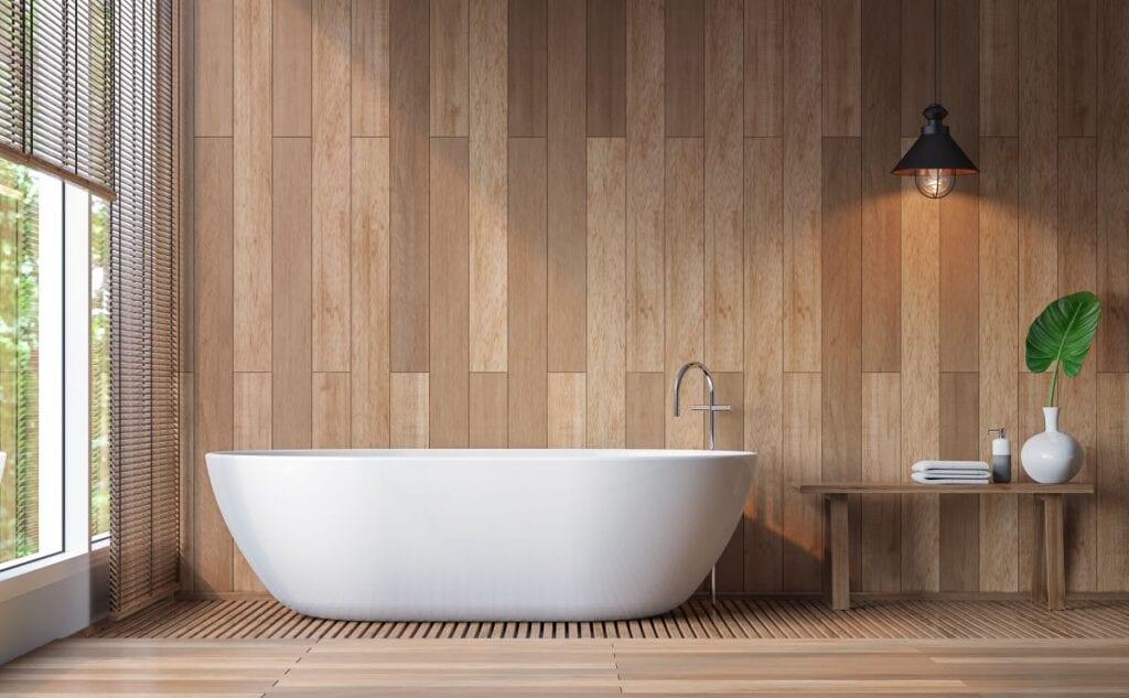 Modern bathroom with wood walls and floors and pristine white bathtub