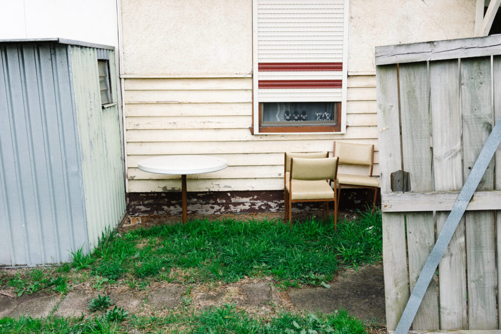 An unkept suburban backyard in Melbourne, Sutralia with rusted chairs and table an old metal shed and broken wooden door.