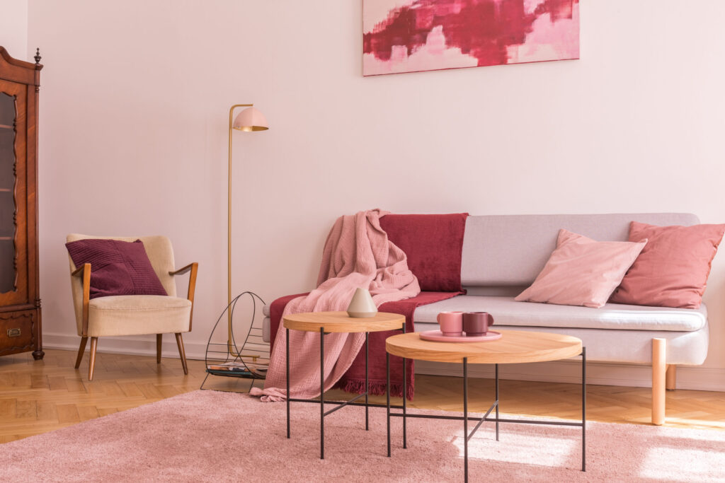 Two wooden coffee tables next to modern grey sofa with pillows and blankets in lovely pastel pink living room interior