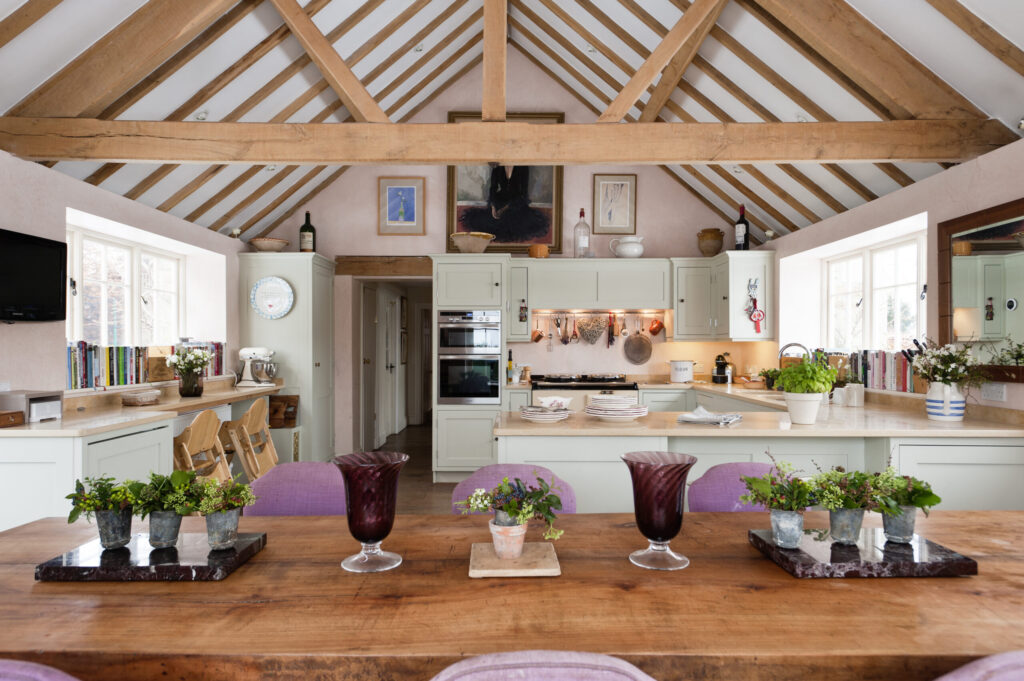 Open plan kitchen diner with pitched ceiling and beams. The kitchen units were made by Kevin Anderson and painted in Dulux Gooseberry