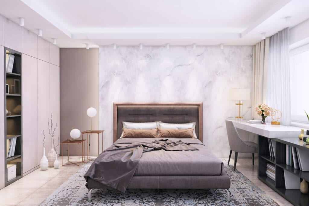 Modern bedroom interior with large pastel colored bed and pillows with big blank marble wall for copy space in the background.