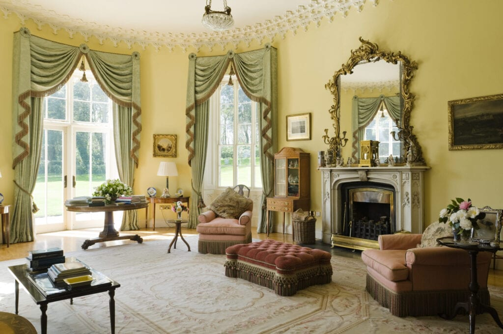 Pale green fringed curtains in yellow drawing-room with gilt framed mirror, mantelpiece and red tufted ottoman