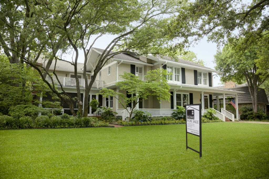 view of residential home with for sale sign on the large green front lawn