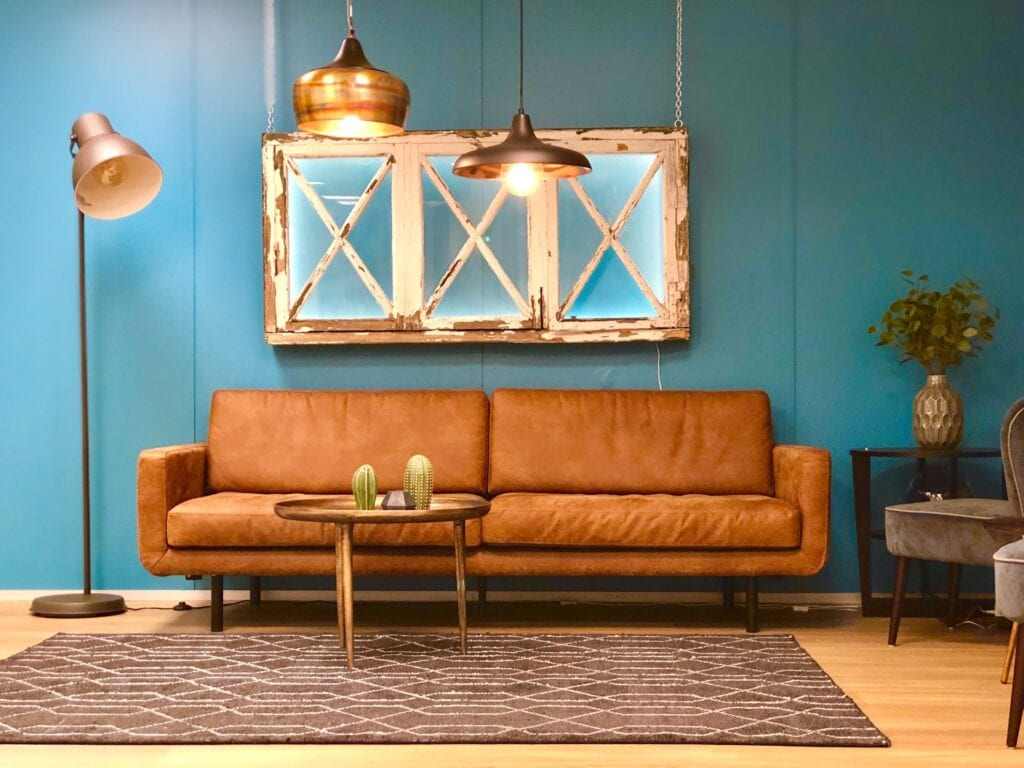 Blue painted living room with brown couch