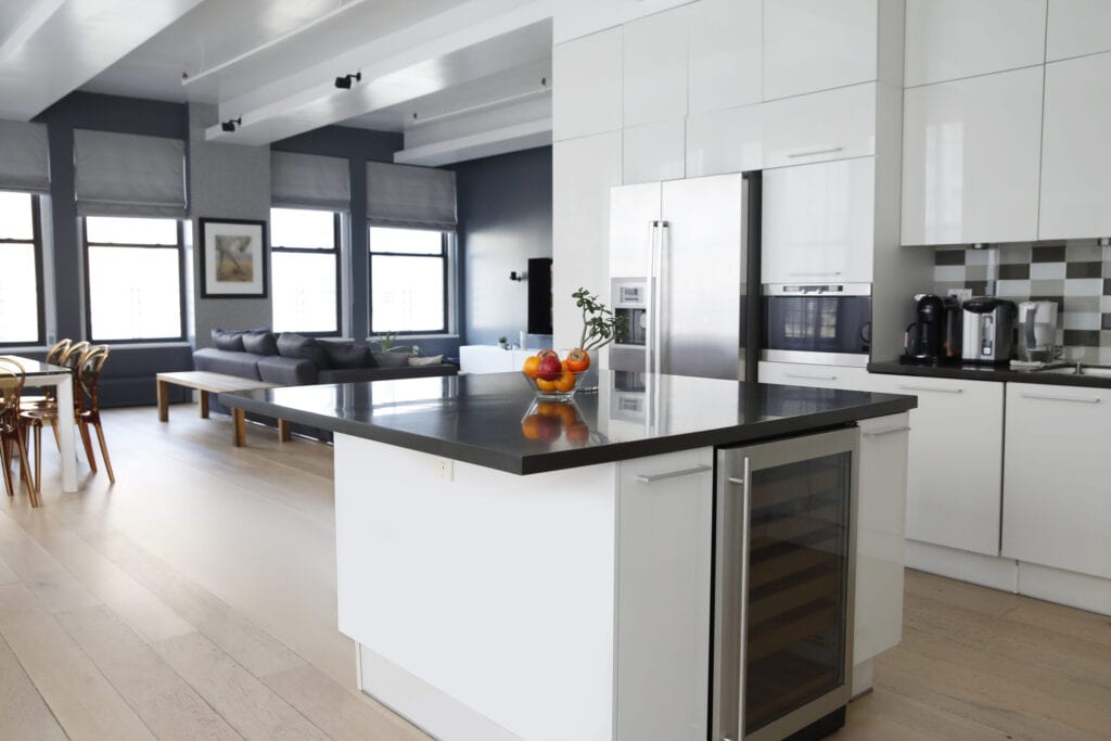 Interior view of modern kitchen and living room, with white cabinets in loft apartment.