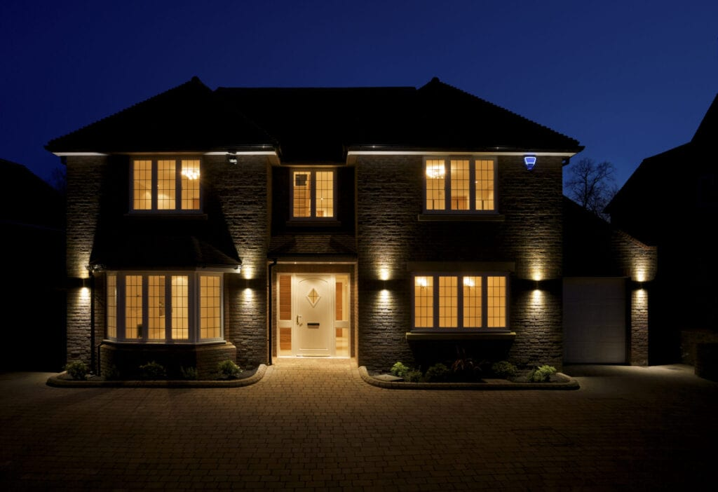 a view of the front and driveway of a lovely double fronted luxury new home, taken at dusk with all of the interior and exterior lights switched on. The branding on the alarm box has been changed to a fictional text.