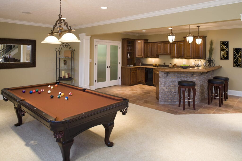 Recently finished residential lower level game room and bar with pool table and stools.