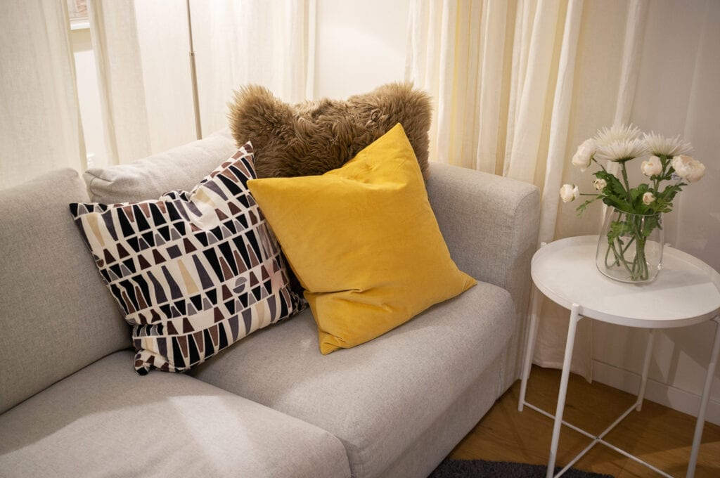 Decorative pillows on light gray textile couch with white side table and flowers - cozy interior home design