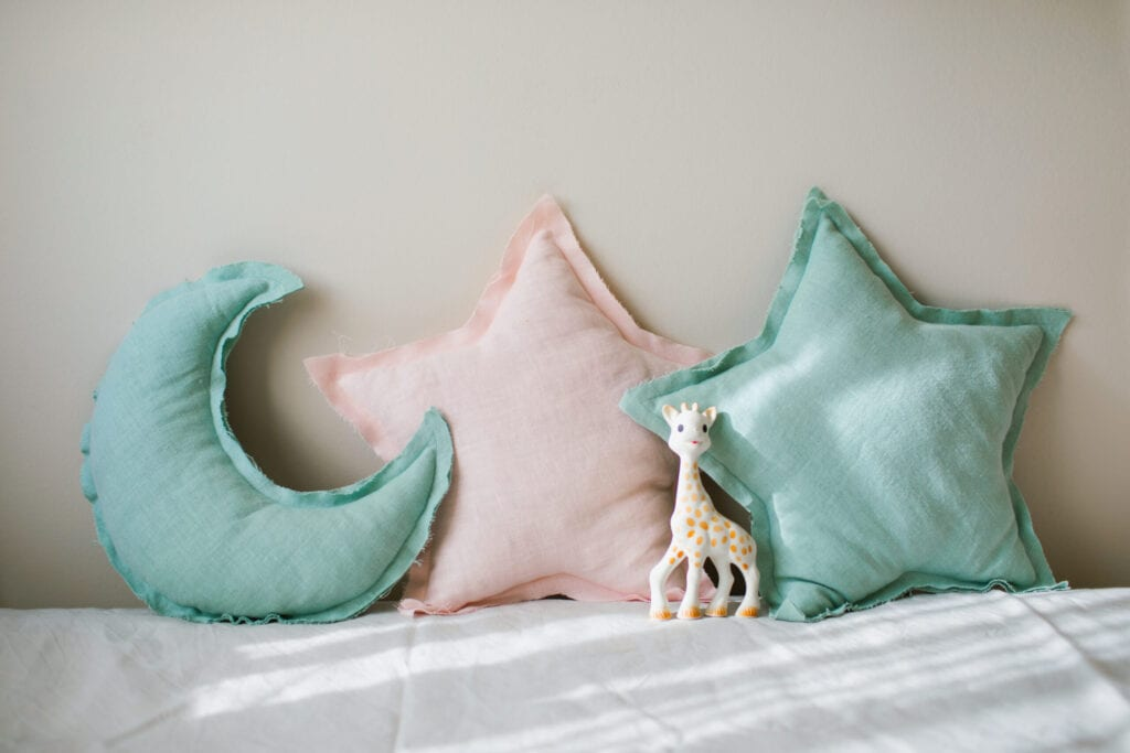 Linen blue and pink moon and star pillows toy on light bedding over beige background. Decorative baby cushions on nursery.