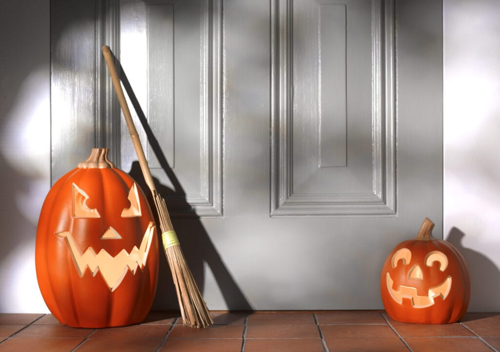 nighttime early evening, lit pumpkins waiting on doorstep for trick and treating time