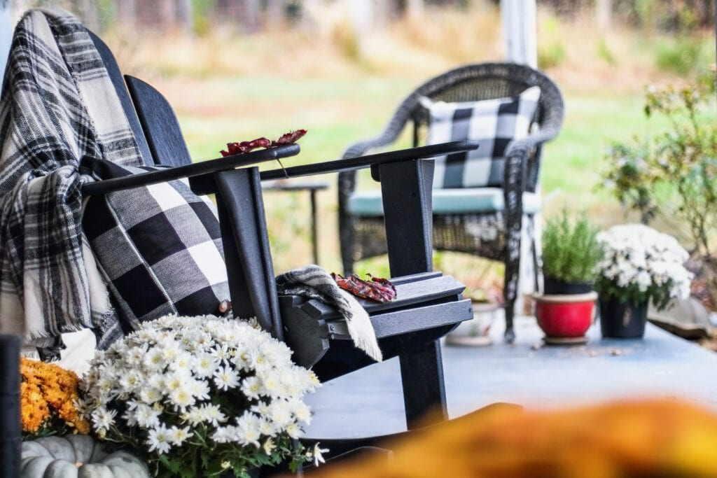 Adirondack rocking chair with traditional style buffalo check blanket and pillows on a porch or patio decorated for autumn with heirloom gourds and white and orange mums. Selective focus with garden blurred in the background.