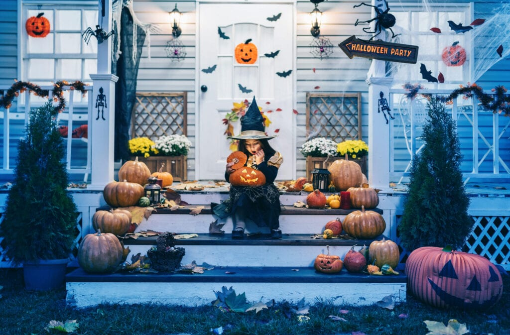 Little girl in witch costume sitting on the stairs in front of the house and holding Jack-o-Lantern Pumpkins on Halloween trick or treat