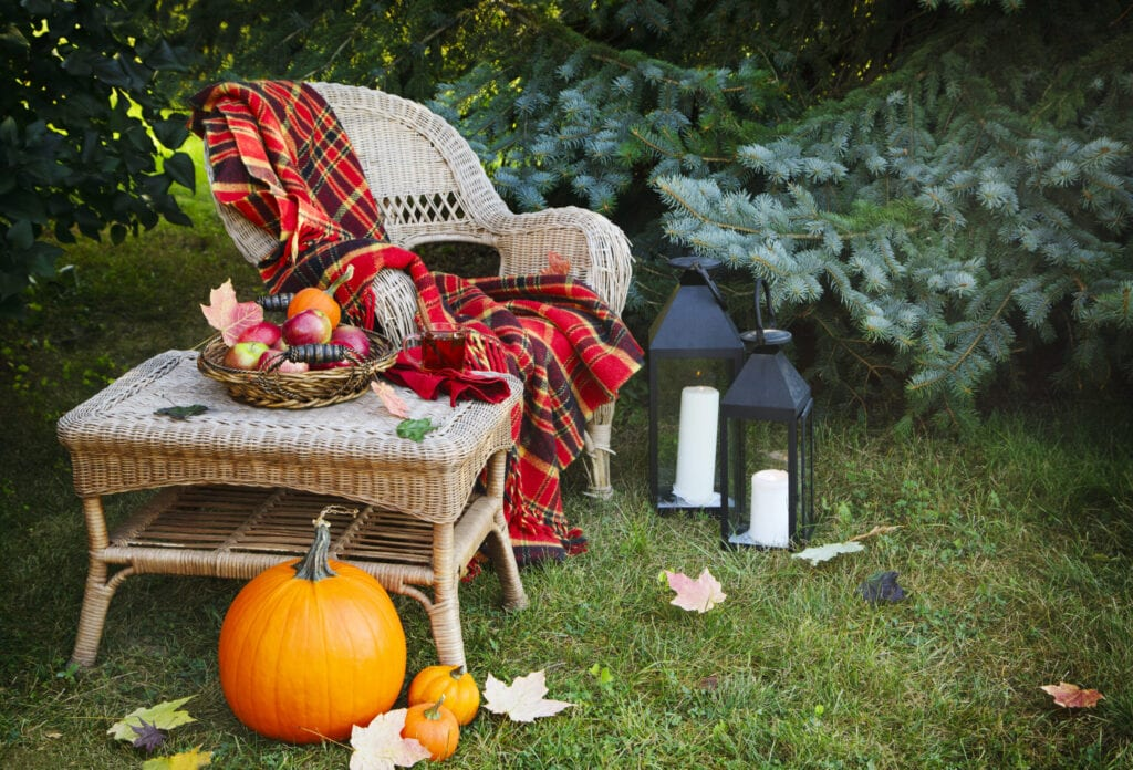 Cup of tea and apples on table and chair in autumn garden