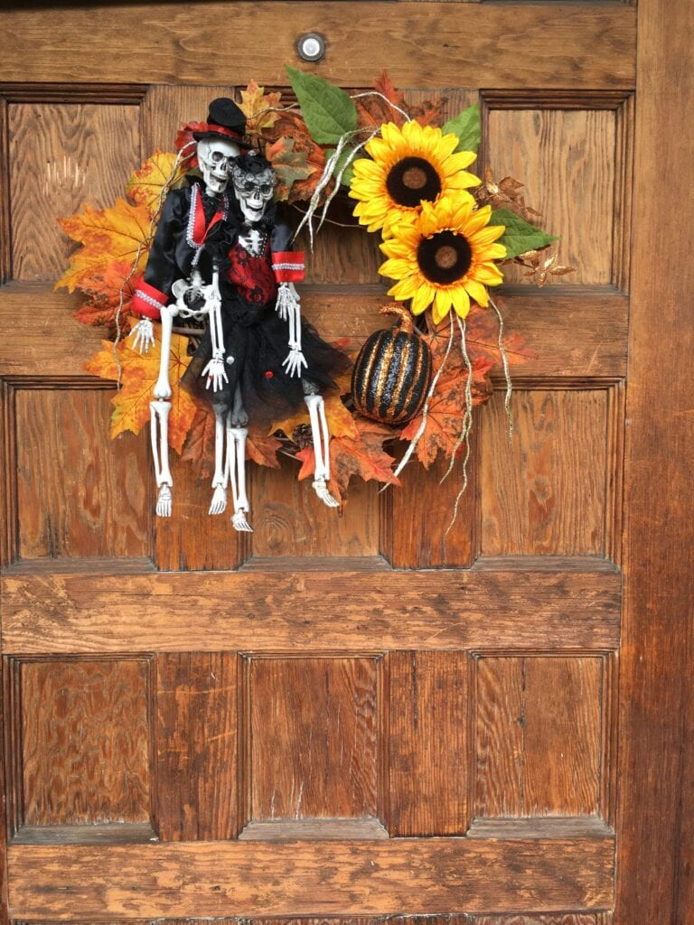 Homemade wreath with Day of the Dead skeletons, fall leaves, sunflowers and pumpkin.