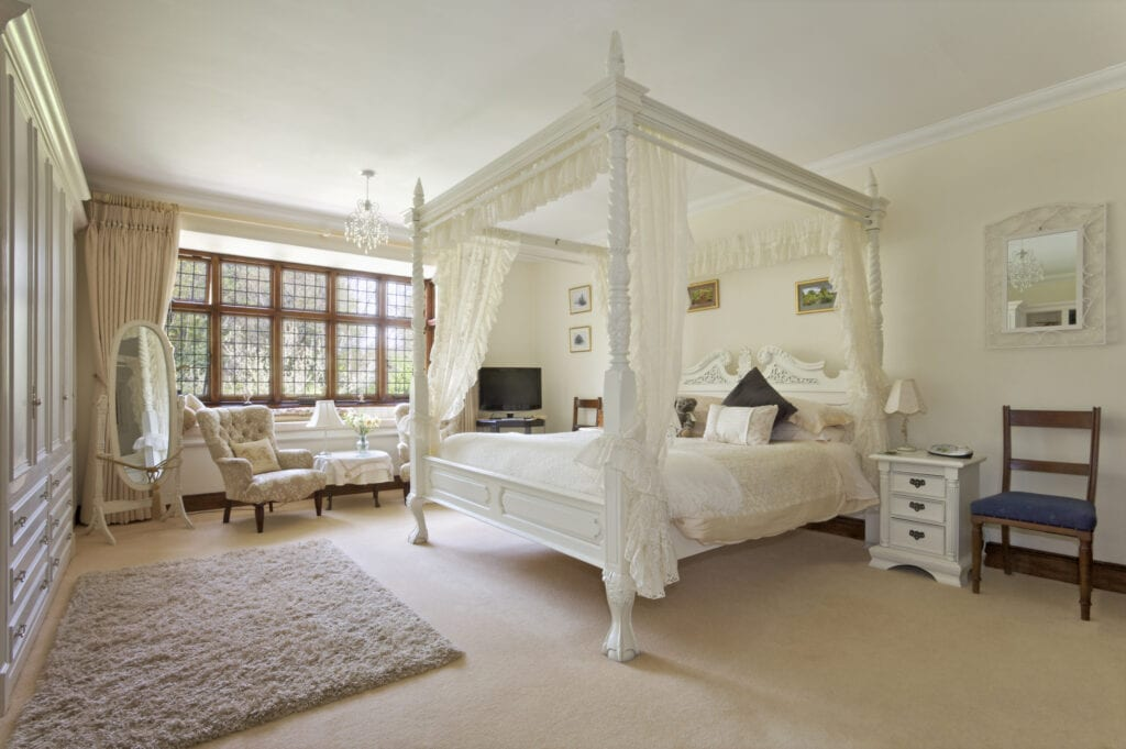 White four-poster bed in a neutral bedroom