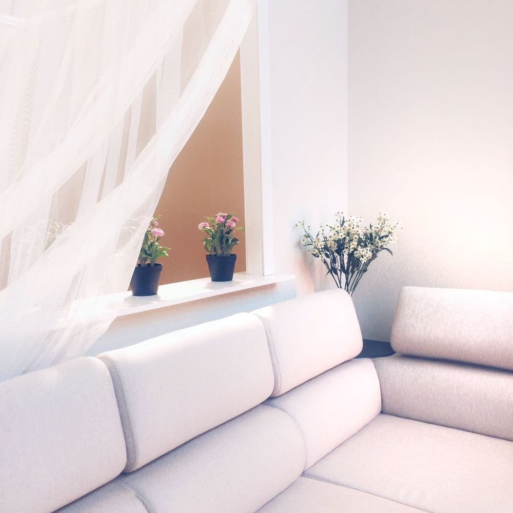 The white color of the couch, walls, and curtains creates harmony and unity in the home