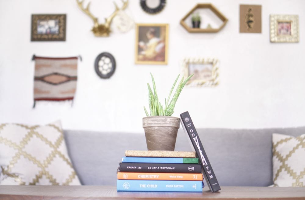 Close up of books and plant on coffee table, gallery of pictures on the wall
