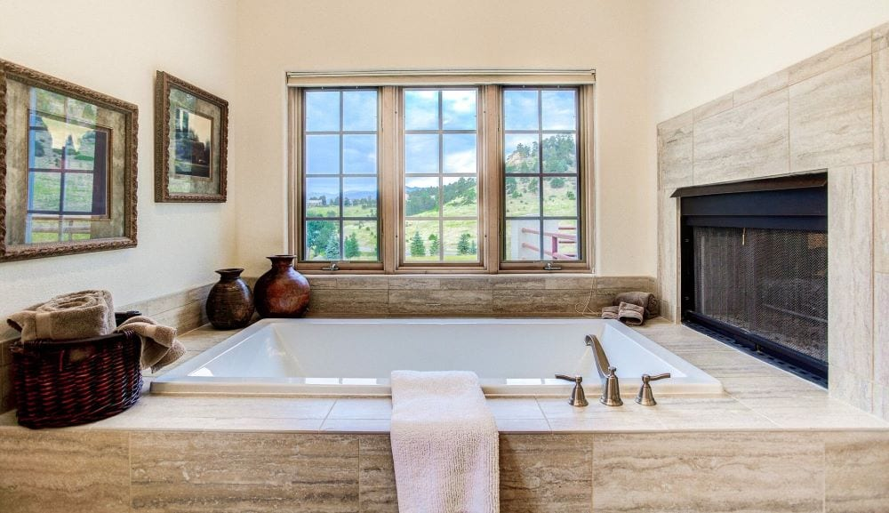 Luxury bathtub with natural light from window and fireplace