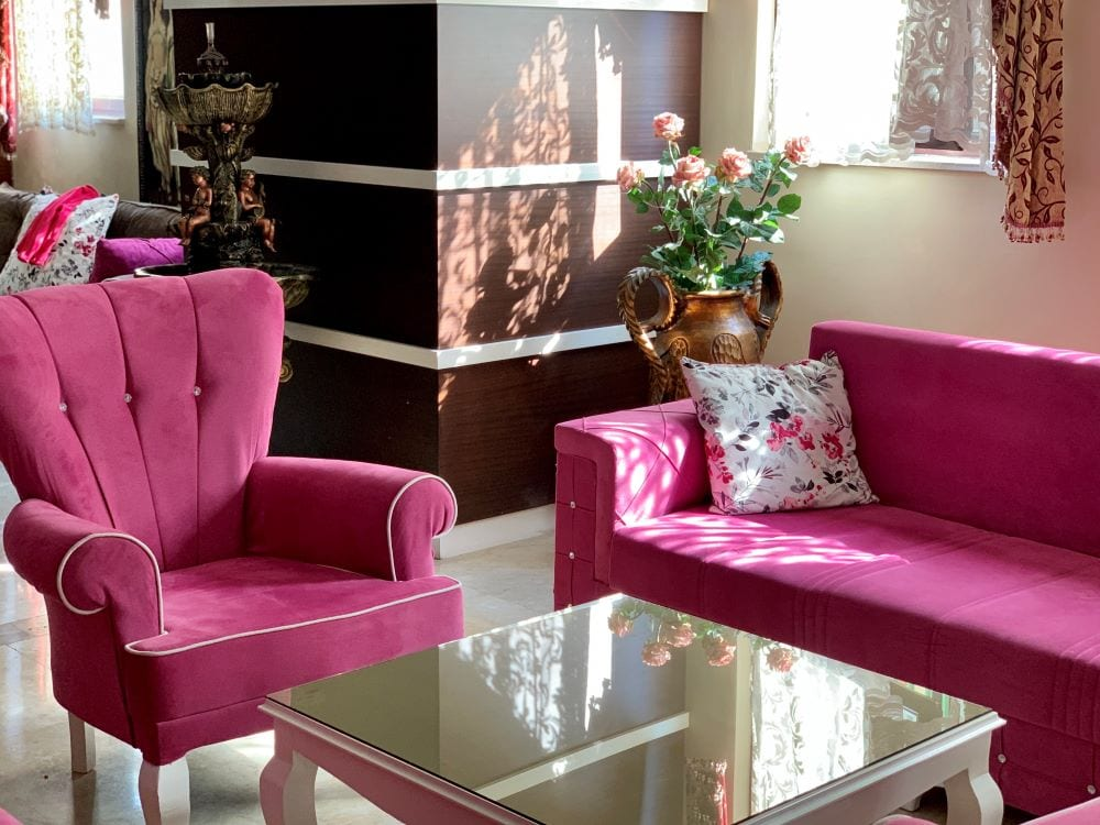 Living room with bright pink couch and chair