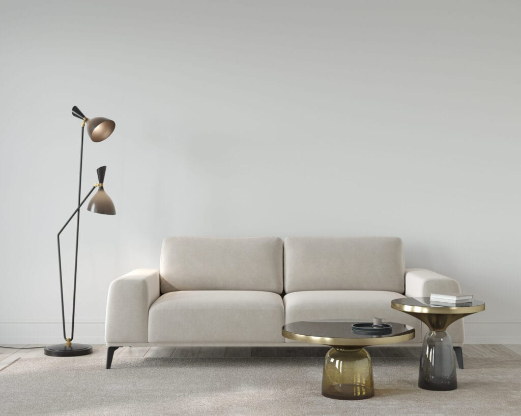 Living room or reception room interior in beige color, with a soft sofa, stylish floor lamp and glass tablesr