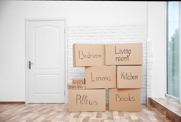 Labeled moving boxes stacked in empty room