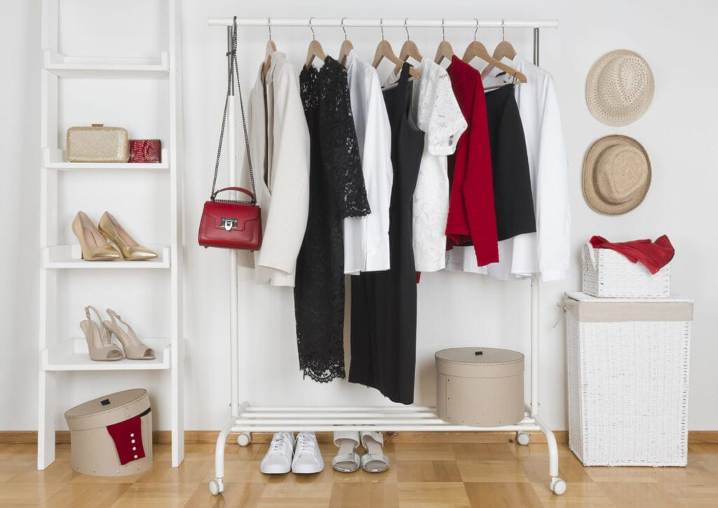 Modern wardrobe interior with different female clothes, hats and shoes