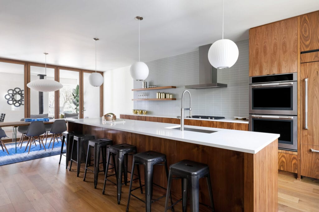 Modern kitchen with black metal barstools and wood island with white countertops
