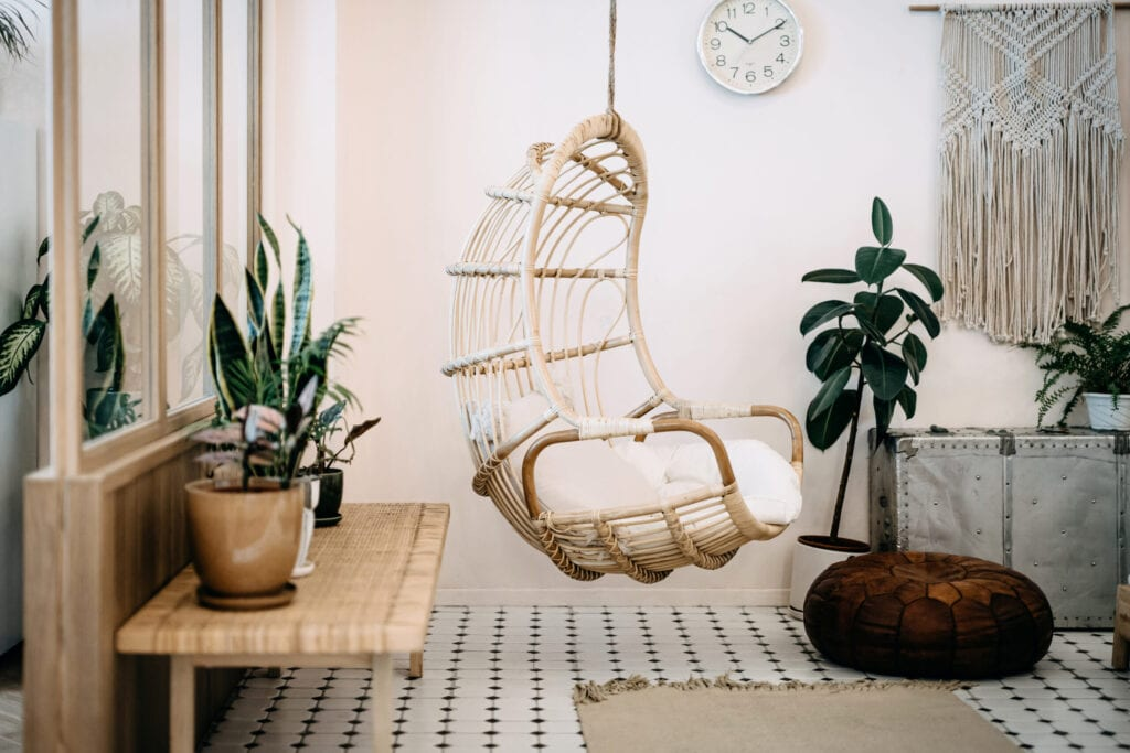 Cozy hanging chair in the loft living room with stylish and bohemia design. Well designed and decorated with an assortment of interesting plants