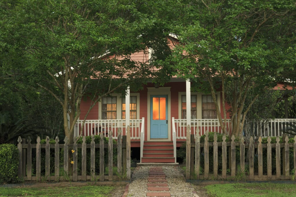 Cottage with weathered picket fence at twilight, Lousianna, USA