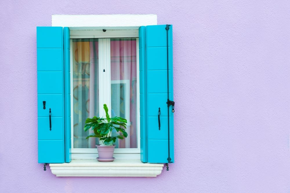 Close up of window with blue shutters against lavender wall