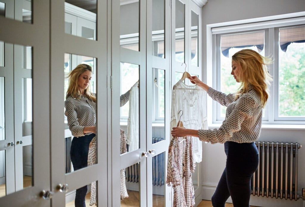 Shot of a woman getting dressed in a long walk in closet full of mirrors