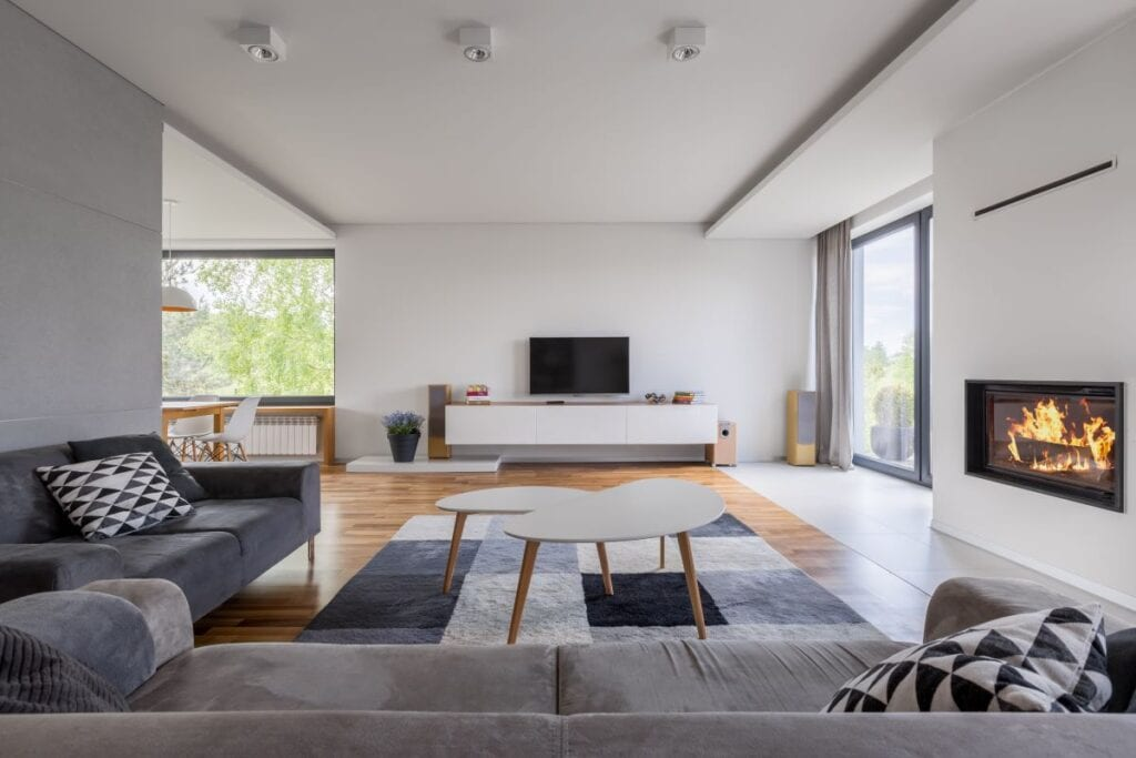 Modern living room with metal fireplace mounted in wall