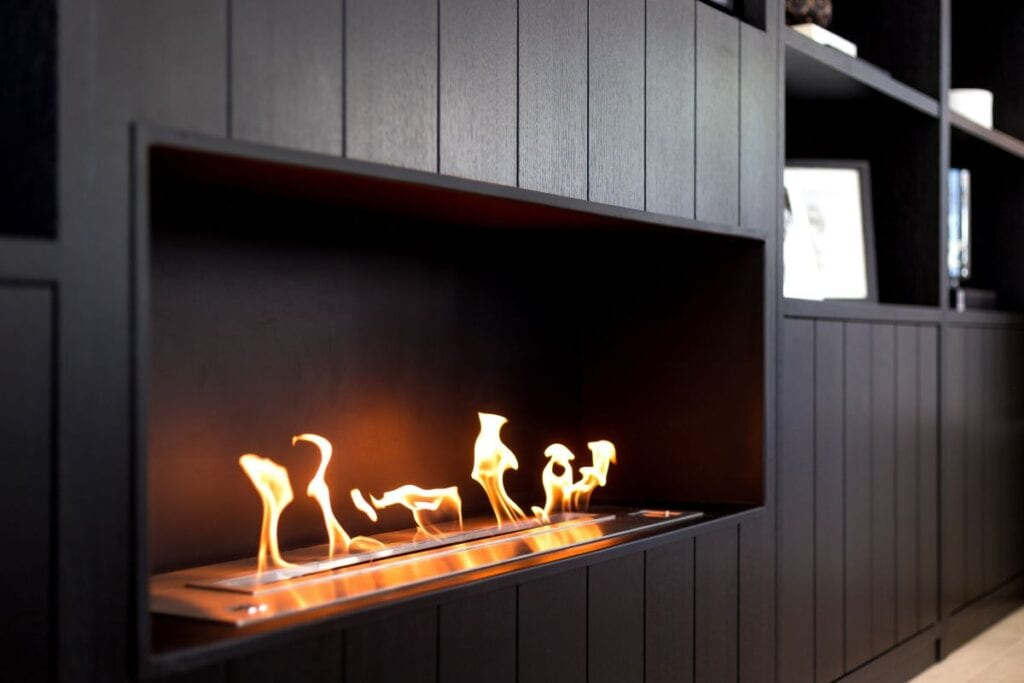 Dark wood fireplace with built in shelving