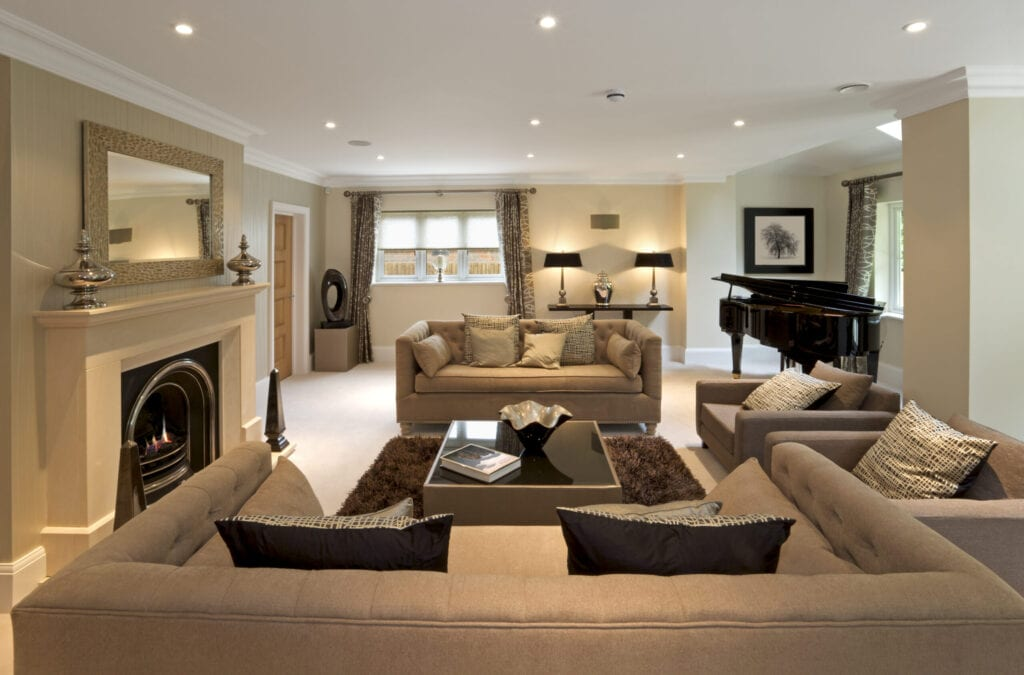 Luxurious living room in an expensive new home that has been decorated and furnished by a leading Interior Designer. The room comprises two large double seat and two single seat settees, a beautiful lit fireplace, a grand piano and lots of elegant silk cushions.