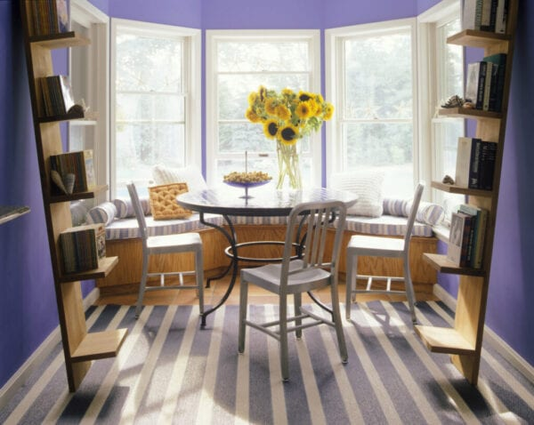 Small dining room with bay window and leaning bookshelves