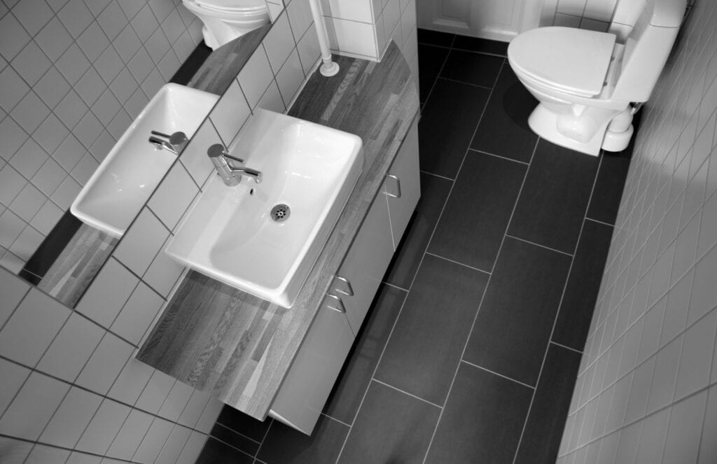 """Small and narrow bathroom seen from above. There is a mirror to the left, where part of the bathroom is """"mirrored""""."""