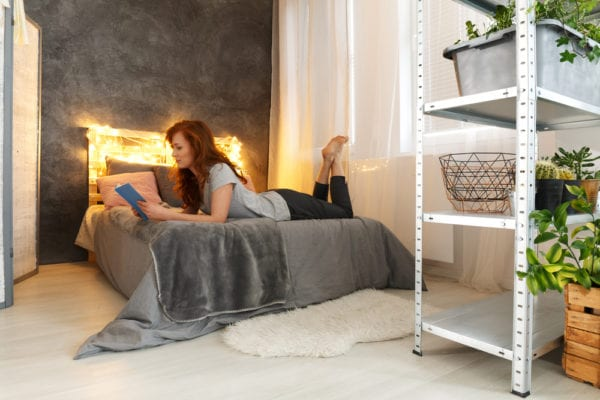 Female sits on bed of her dorm room with cool headboard behind her