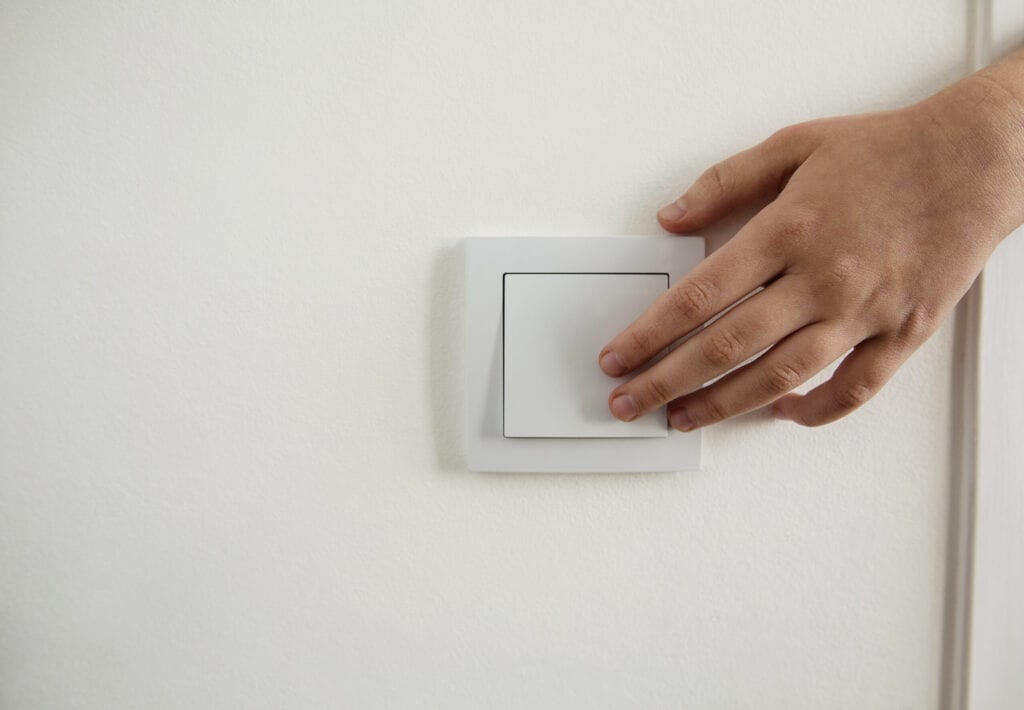 Cropped hand pressing light switch