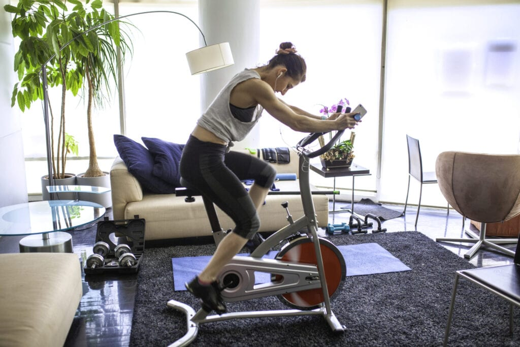 Home Gym under the quarantine, we see a woman using her mobile phone while riding her stationary bike in her apartment, she has conditioned her space in order to keep doing exercise, during the quarantine time of covid19