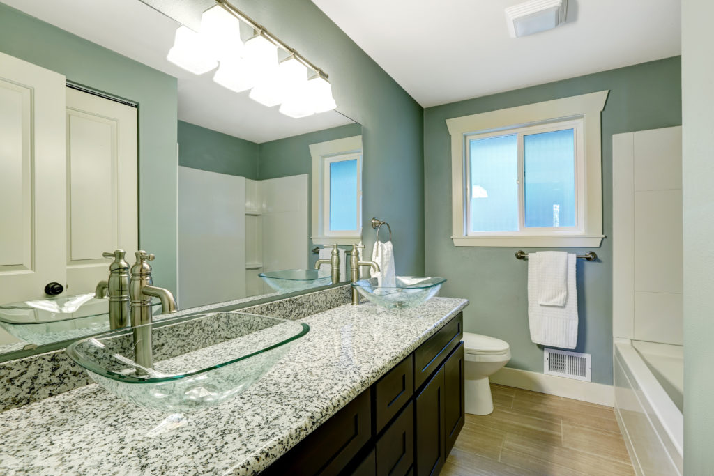 Cerulean bathroom with granite counter and wide mirror