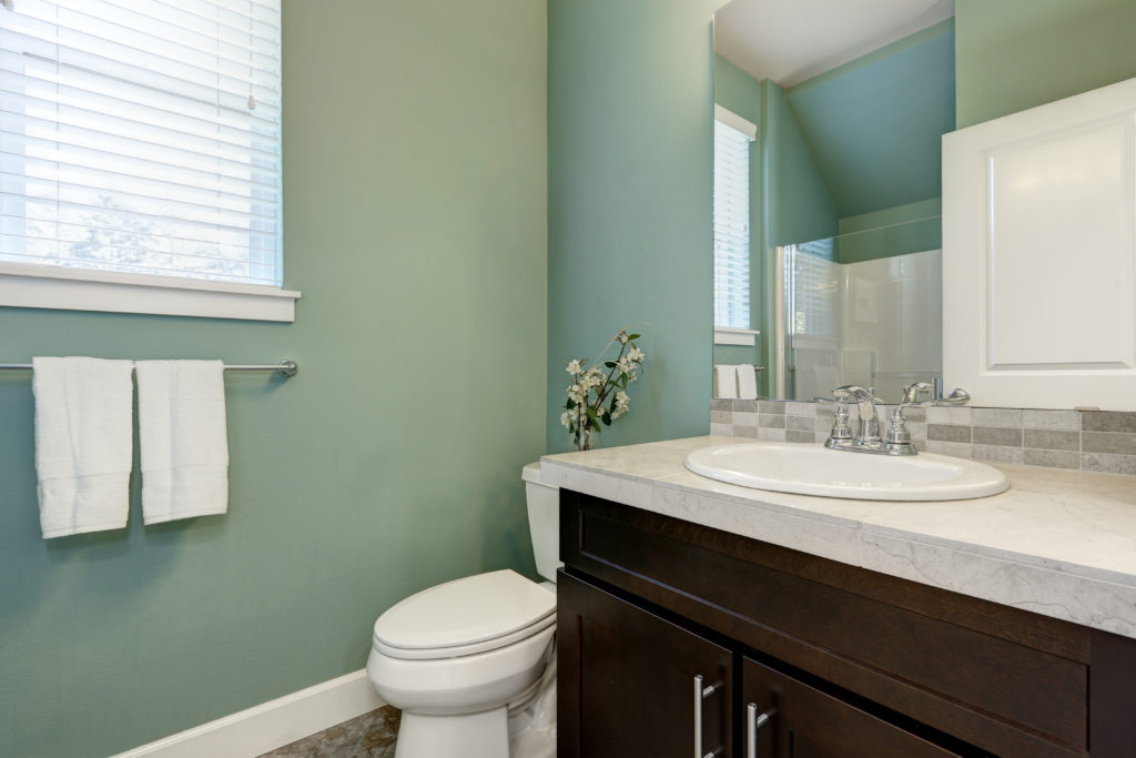 Mint green bathroom with brown cabinets