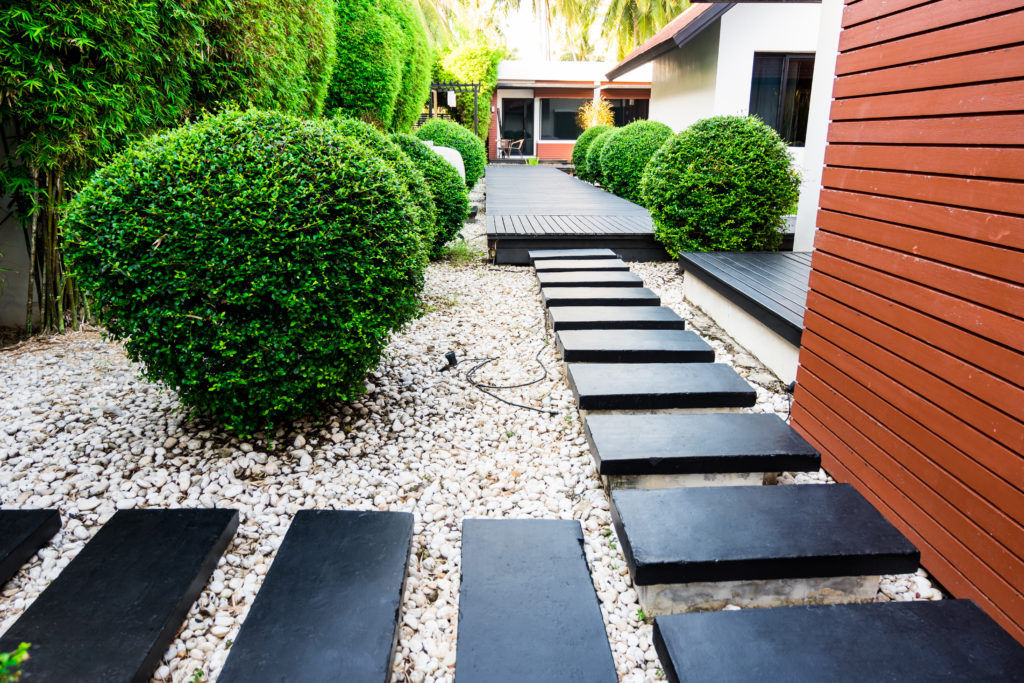 Lawn walkway landscaped with large black stones and white pebbles