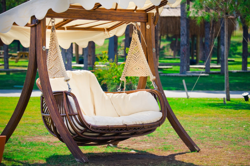 Shaded bench swing in backyard