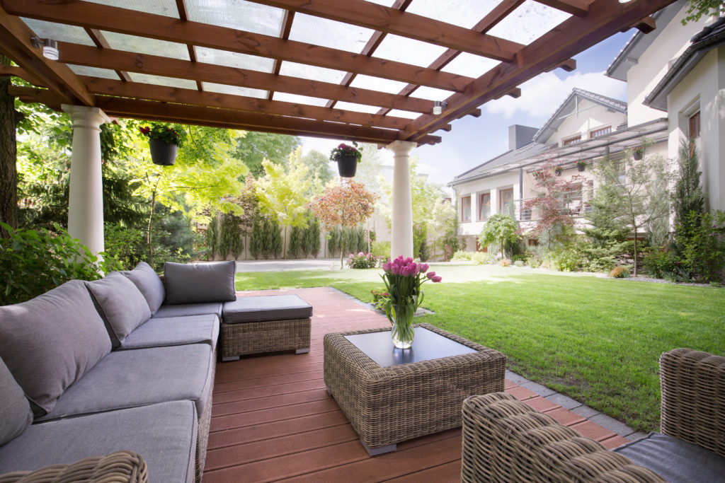 Covered backyard patio with wicker table and sectional