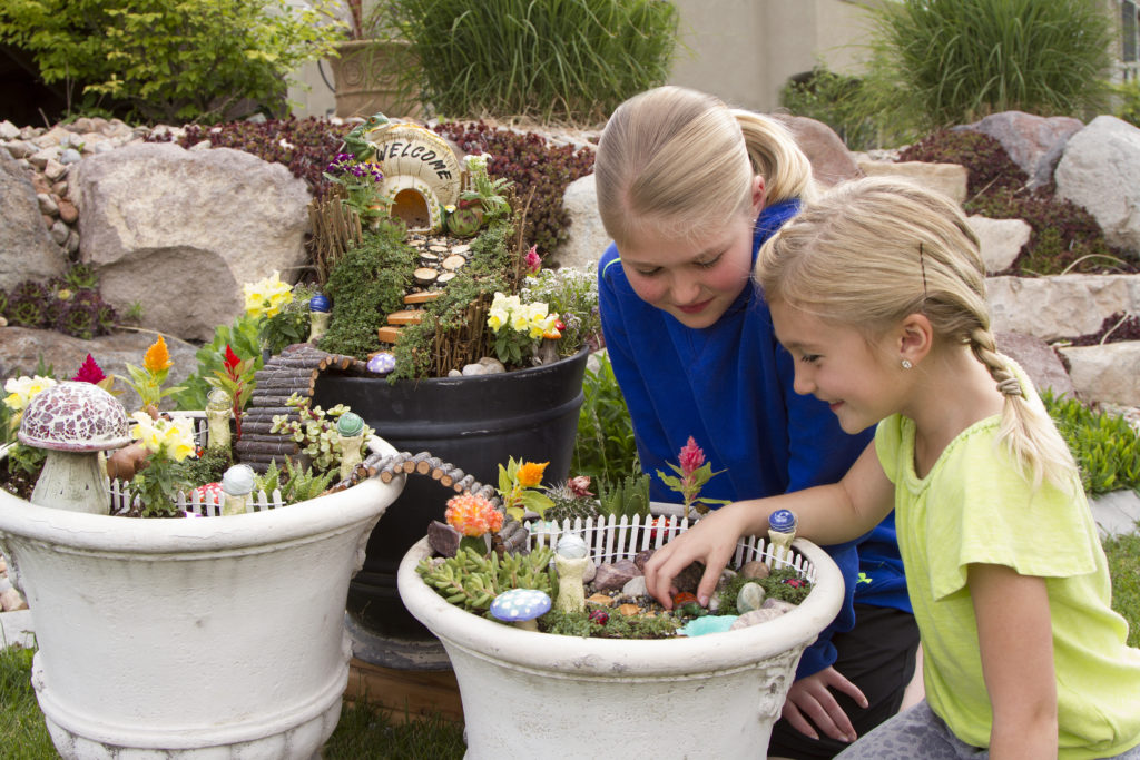 Two young girls creating a fairy garden in a ceramic pot